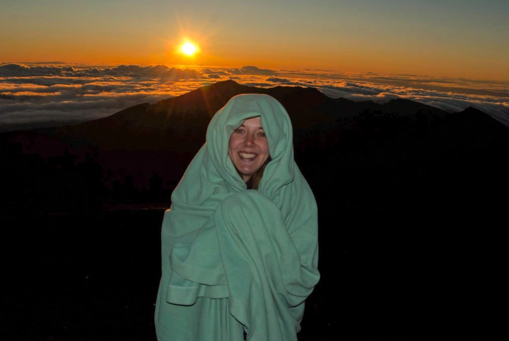 Person wrapped in a blanket watching sunrise at Haleakala