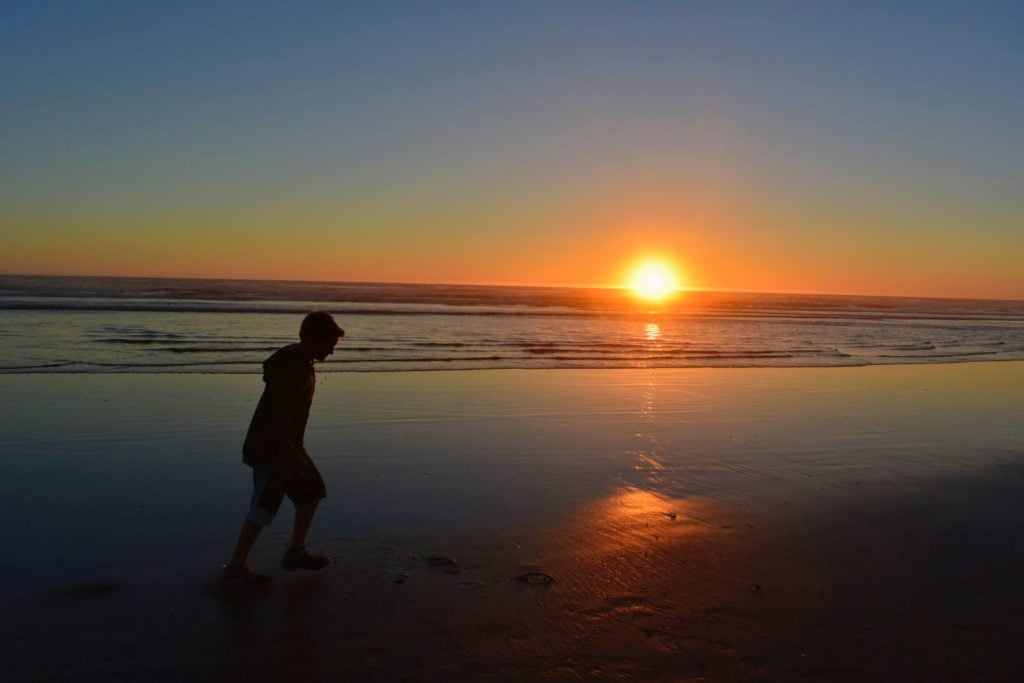 boy walking on beach at sunset