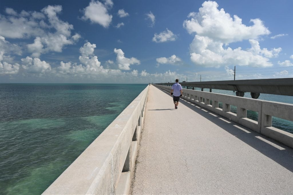 man walking up old seven-mile bridge in Florida Keys