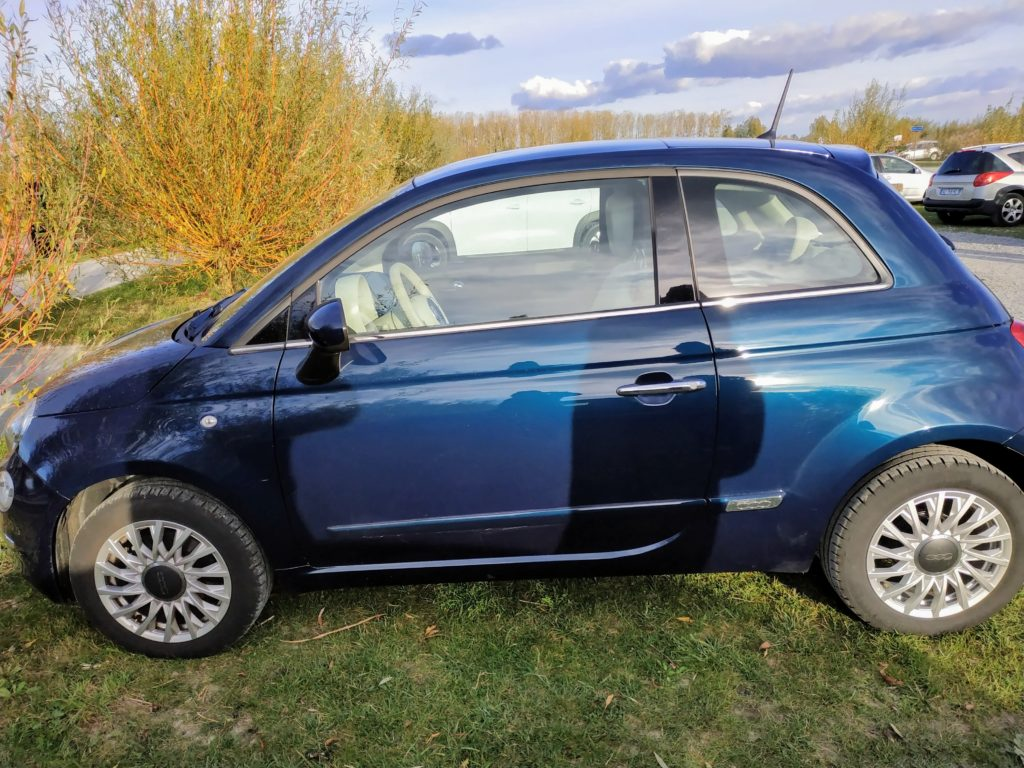 Blue Fiat 500 rented in Normandy.