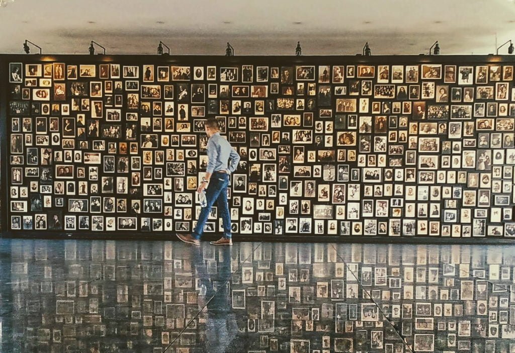 wall of photographs from those murdered at Auschwitz