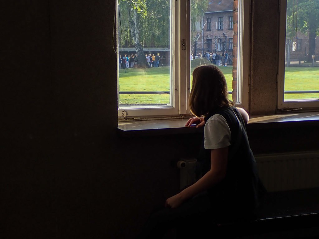 Woman looking out window at Auschwitz museum