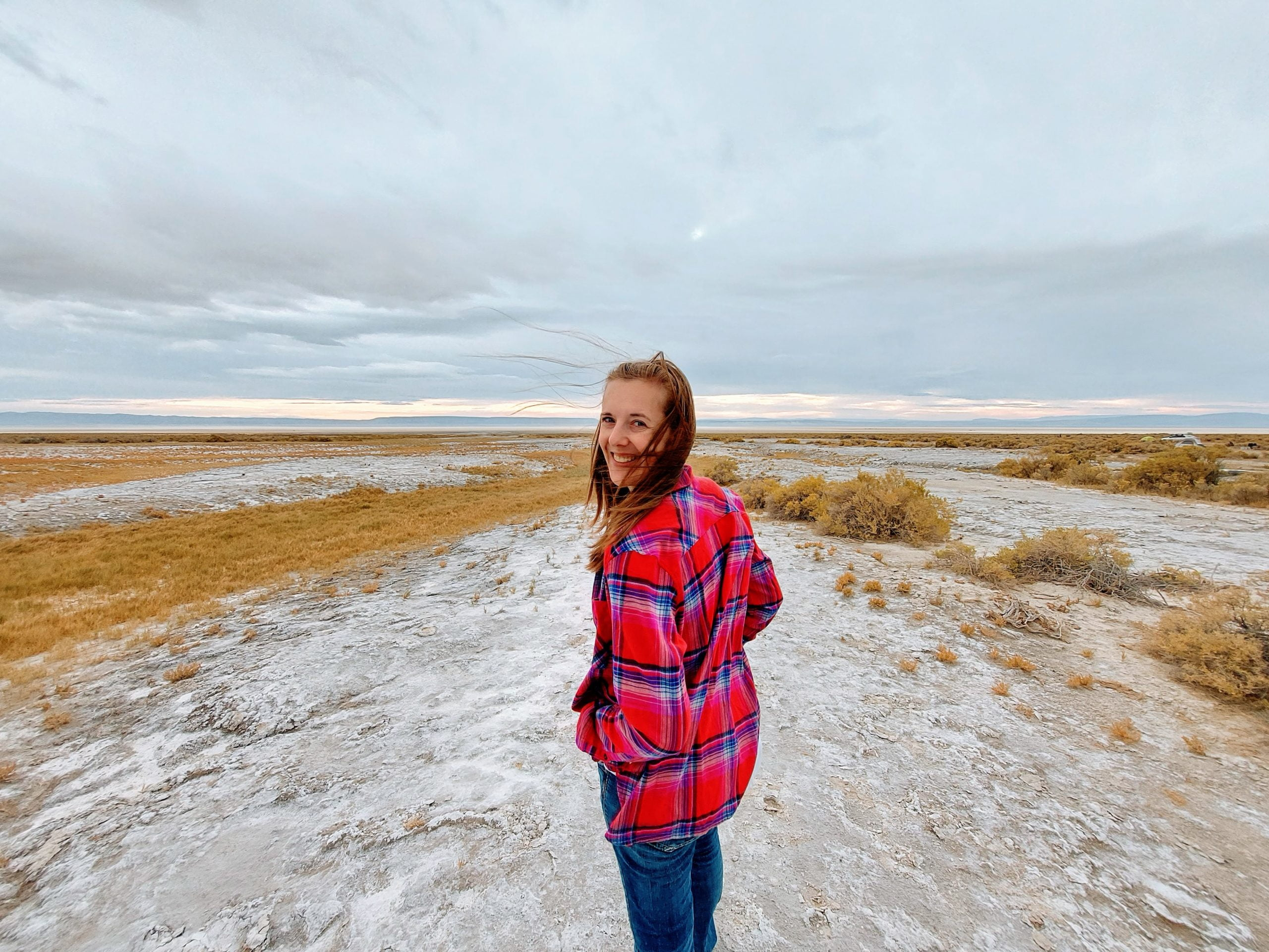 woman standing on white mineral rich soil in the desert