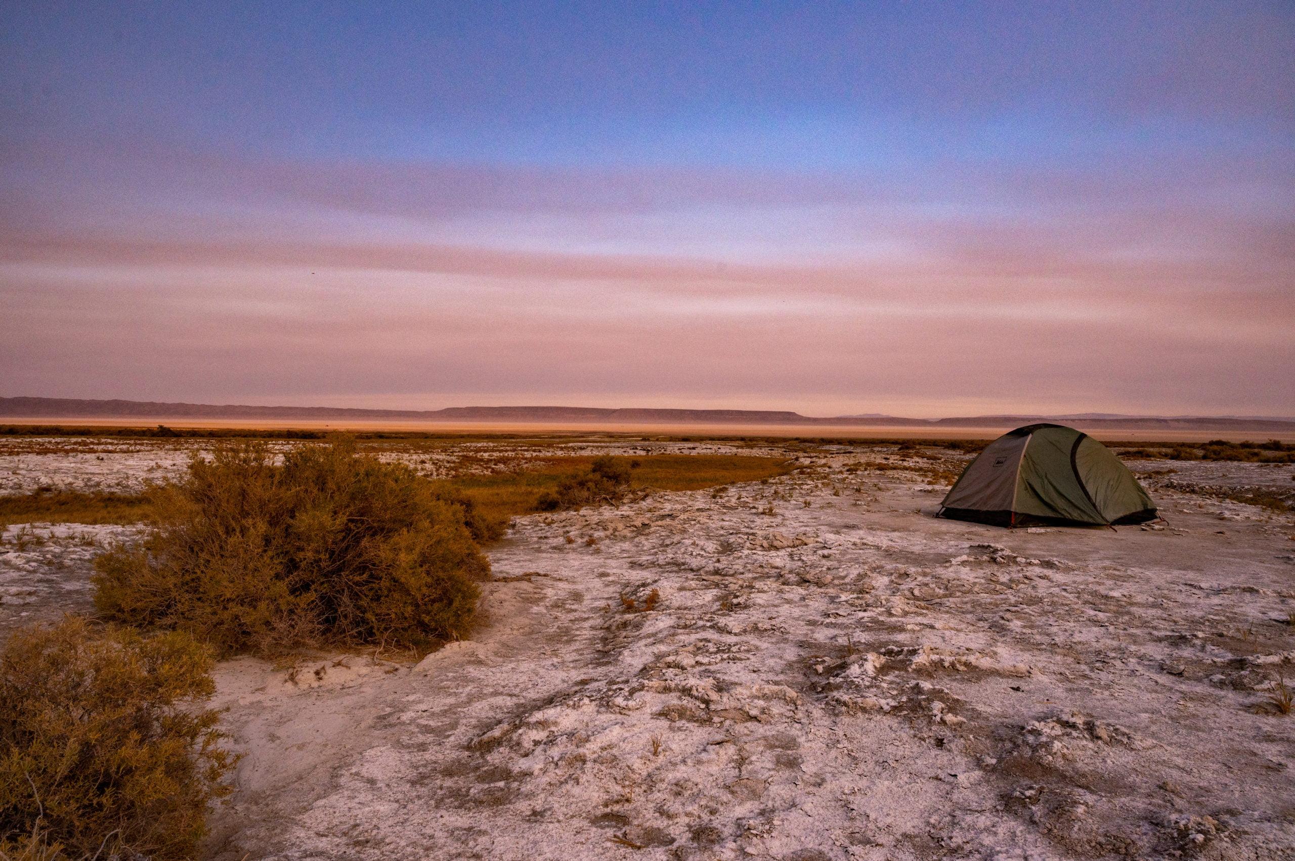 tent in desert at sunset